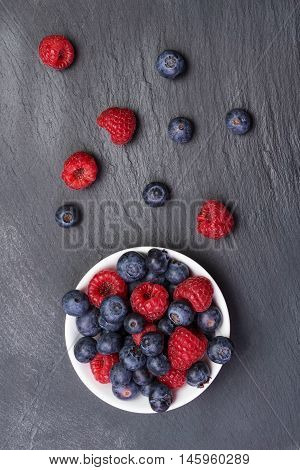 fresh raspberries and bilberry berries scattered on black background.Top view