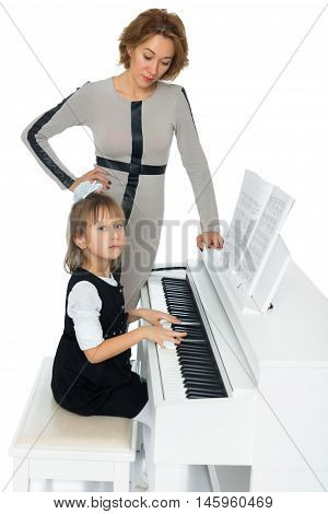 Diligent little girl at a music school teaching musical notation. Beside her is her teacher - Isolated on white background