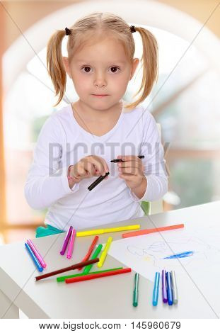 Beautiful little blonde girl with white t-shirts without a pattern, draws markers at the table on a white sheet of paper. The girl is holding a pen . close-up.The concept of pre-school education of the child among their peers . in gaming room with a large