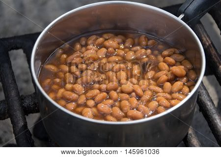A pan of baked beans cooking on a barbecue