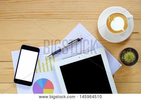Office desk table with blank screen smartphone blank screen tabletpenanalysis chart and cup of coffee .Top view with copy space.Office desk table concept.Office supplies and gadgets on desk table.