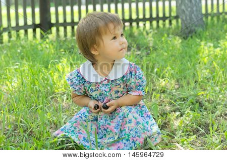 Little Girl On Green Glade Sitting And Smiling With Berries