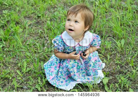 Little Girl On Green Glade Sitting And Eating Berries