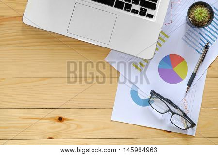 Office desk table with eyeglass laptoppen and analysis chart.Top view with copy space.Office desk table concept.Office supplies and gadgets on desk table.