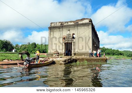 OLD WAT WANG WIWEKARAM SAGKLABURI 12 OCT 2014:Tourists in a long tail boat at the entrance of The Sunken Temple Wat Wang Wiwekaram Kanchanaburi Thailand.