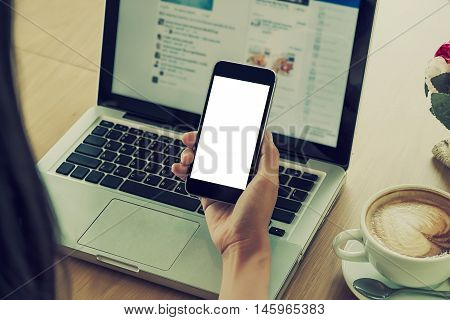 Young woman using smartphone.Beautiful hand holding with blank screen smartphone in cafe.Vintage tone.