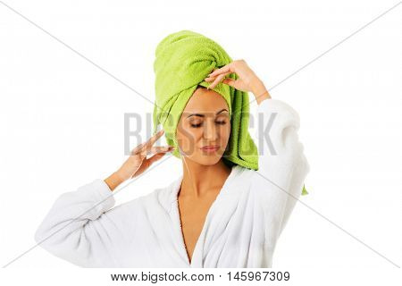 Woman in bathrobe touching her head