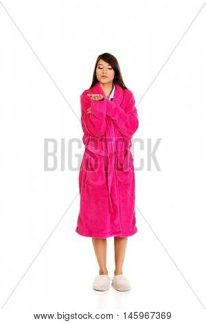 Woman in pink bathrobe showing empty palm.