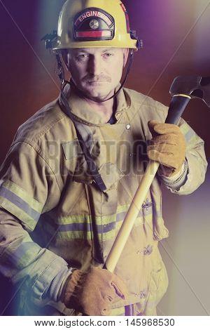 Fireman holding axe wearing uniform