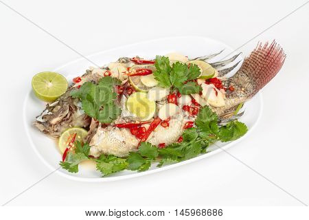 Tilapia fish streamed lemon on white background.