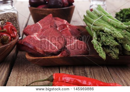 fresh beef meat asparagus greenery spices cutlery wooden table pepper crushed hot chili vegetables bowl served