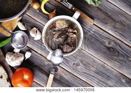 home style beef meat soup vintage country wood table asparagus pepper bell spices bread garlic cutlery eggplant