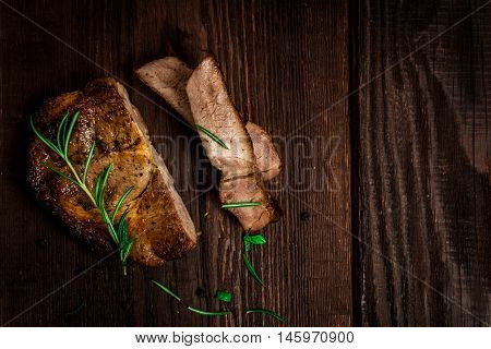 Grilled pork neck steak with rosemary on wood table
