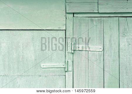Old Cyan Wooden Hangar Door With Metal Hinges.