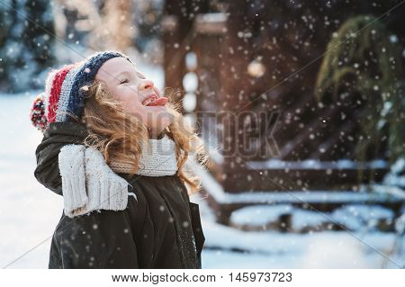 happy child girl catching snowflakes and playing on winter snowy walk in garden seasonal outdoor activities on vacations