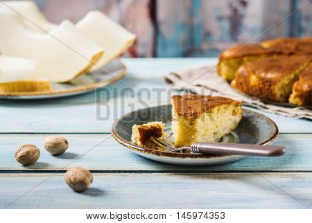 Melon cake on turquoise shabby wooden background with slices of melon and nutmeg. Autumn baking. Selective focus