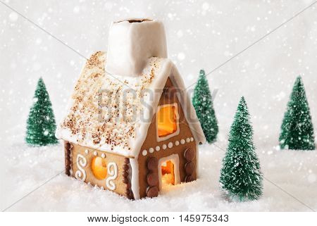 Gingerbread House In Snowy Scenery As Christmas Decoration. Christmas Trees And Candlelight For Romantic Atmosphere. White Background With Snowflakes. Christmas Card For Seasons Greetings