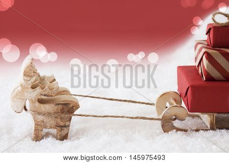 Moose Is Drawing A Sled With Red Gifts Or Presents In Snow. Christmas Card For Seasons Greetings. Red Christmassy Background With Bokeh Effect. Copy Space For Advertisement