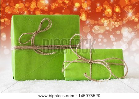 Two Green Christmas Gift Or Present On Snow. Card For Birthday Or Seasons Greetings. Natural looking Ribbon. Background With Complementary Red Orange Bokeh Effect
