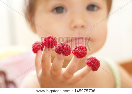 Child With Raspberry On Fingers, Focus On Hands