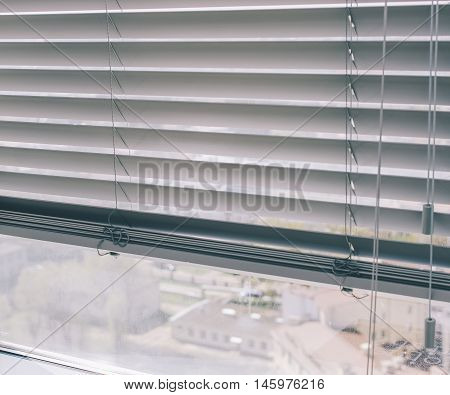 Window blinds on the office window with view on city