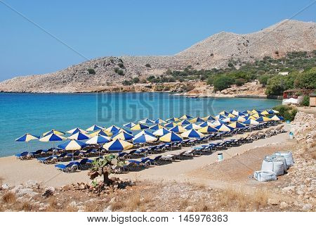 HALKI, GREECE - JULY 20, 2016: Looking down onto Pondamos beach at Emborio on the Greek island of Halki. Pondamos is one of the three main tourist beaches on the small Dodecanese island.