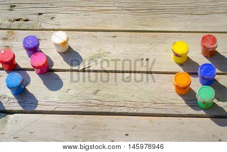 wood background and small jars of paint gouache top view on a sunny day. Background, space for text