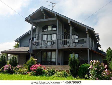 Grey colored house made from finn timber. Flowers grass and good weather with blue sky and clouds