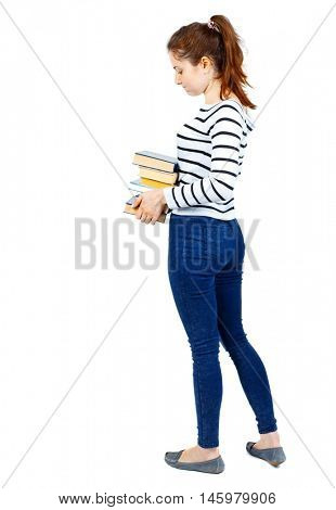Girl carries a heavy pile of books. back view. Rear view people collection. Girl in a striped sweater standing sideways and holding a stack of textbooks.
