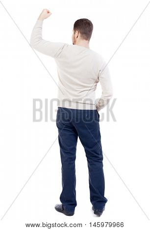 Back view of man. Raised his fist up in victory sign bearded man in a white warm sweater triumphantly held up a hand.