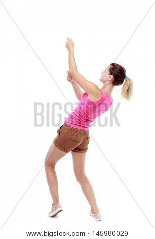 back view of standing girl pulling a rope from the top or cling to something. Isolated over white background. Sport blond in brown shorts pulls the rope from above.