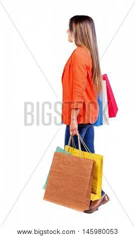 side view of going woman with shopping bags . girl in a red jacket goes to the side with paper bags.