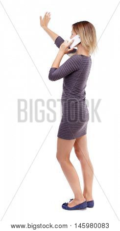 side view of a woman walking with a mobile phone. back view ofgirl in motion. . Isolated over white background. Blonde in violet short dress talking on the white smartphone.