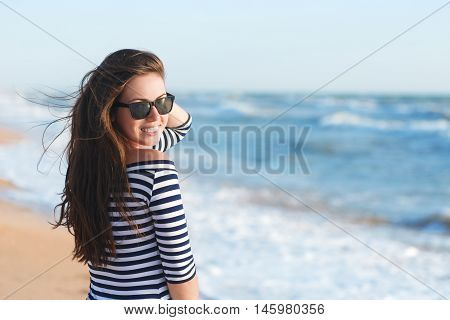 summer holidays and vacation concept happy girl in striped dress standing on the ocean or sea beach with copy space horizontal shot. Portrait of stylish woman with tan skin and hair in the wind in striped dress and sunglasse posing on the beach.