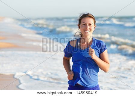 portrait of fitness woman running by the ocean or sea beach at sunrise with copy space. Running woman jogging on beach listening to music in earphones. Fitness and heath care concept.