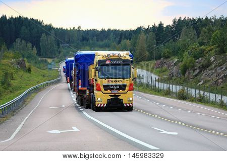ORIVESI FINLAND - SEPTEMBER 1 2016: Yellow MAN V8 semi truck of Silvasti leads the convoy of wide load road transports in the evening along scenic highway in Central Finland.