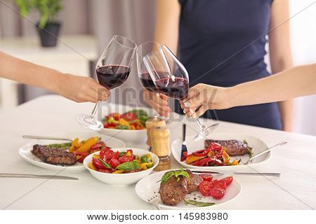 Woman clinking glasses with wine at lunch time