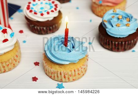 Delicious cupcake with candle on white wooden background