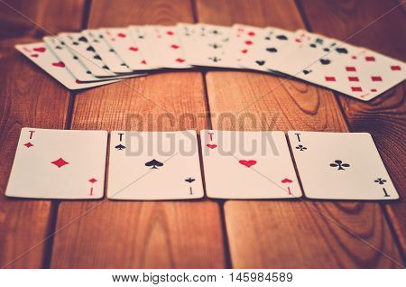 4 aces lying on a wooden background (vintage)