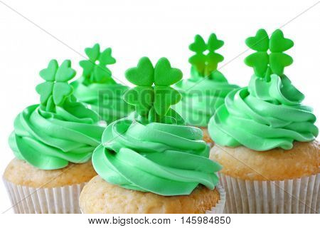Tasty cupcakes with clover, on white background. Saint Patrics Day concept
