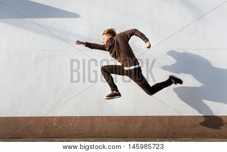 Man jumps like superman on white wall. City concept