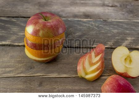 Mix of apple and orange on a wooden desk .