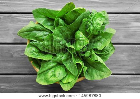 Fresh sorrel in bowl on wooden table