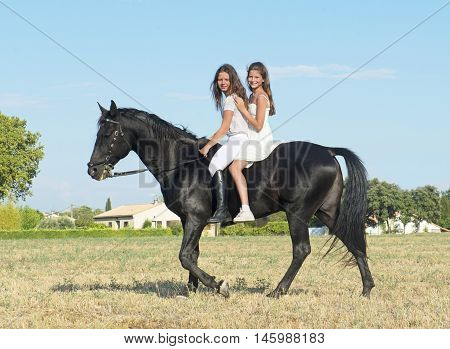 young girls riding a black stallion in a field
