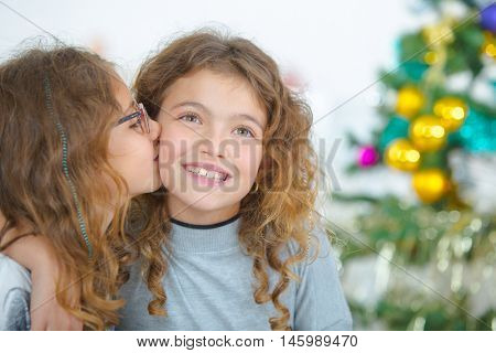 Young girl kissing cheek of friend