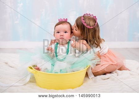 pretty older sister kissing younger sister on cheek. A sweet girl with pink princess crown on her head