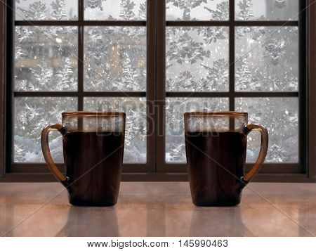 Two mugs with a hot drink - tea or coffee on the window sill of the window. Outside winter snow snow patterns on glass