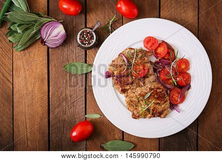 Juicy Pork Steak With Rosemary And Tomatoes On A White Plate. Top View