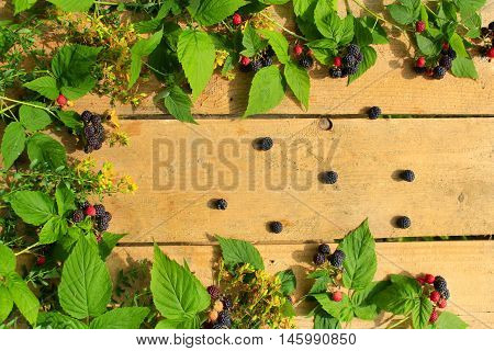 black raspberry with berries and leaves on the light wooden background