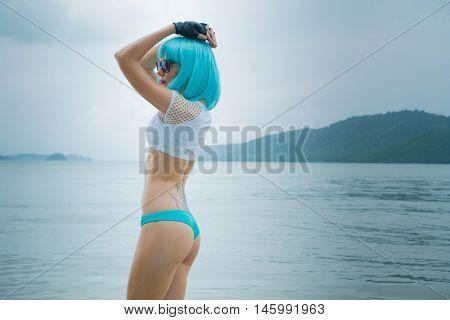 Sexy beautiful woman in modern futuristic style posing in the sea. Creative look of woman wearing bikini, blue wig, black leather fingerless gloves in the water